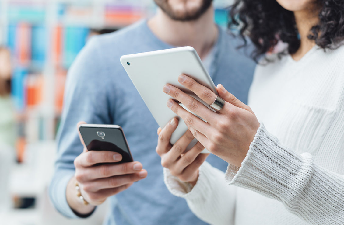 A man holding cell phone and a woman holding tablet